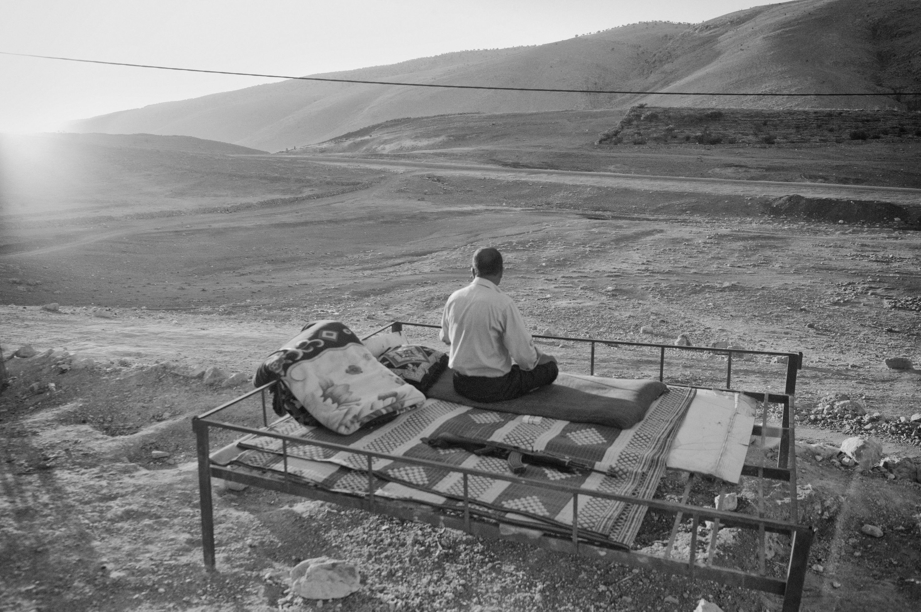 Iraq september 17, 2014, Mount Sinjar, A local Yazidi wakes up with his rifle next to him. Foto Eddy van Wessel