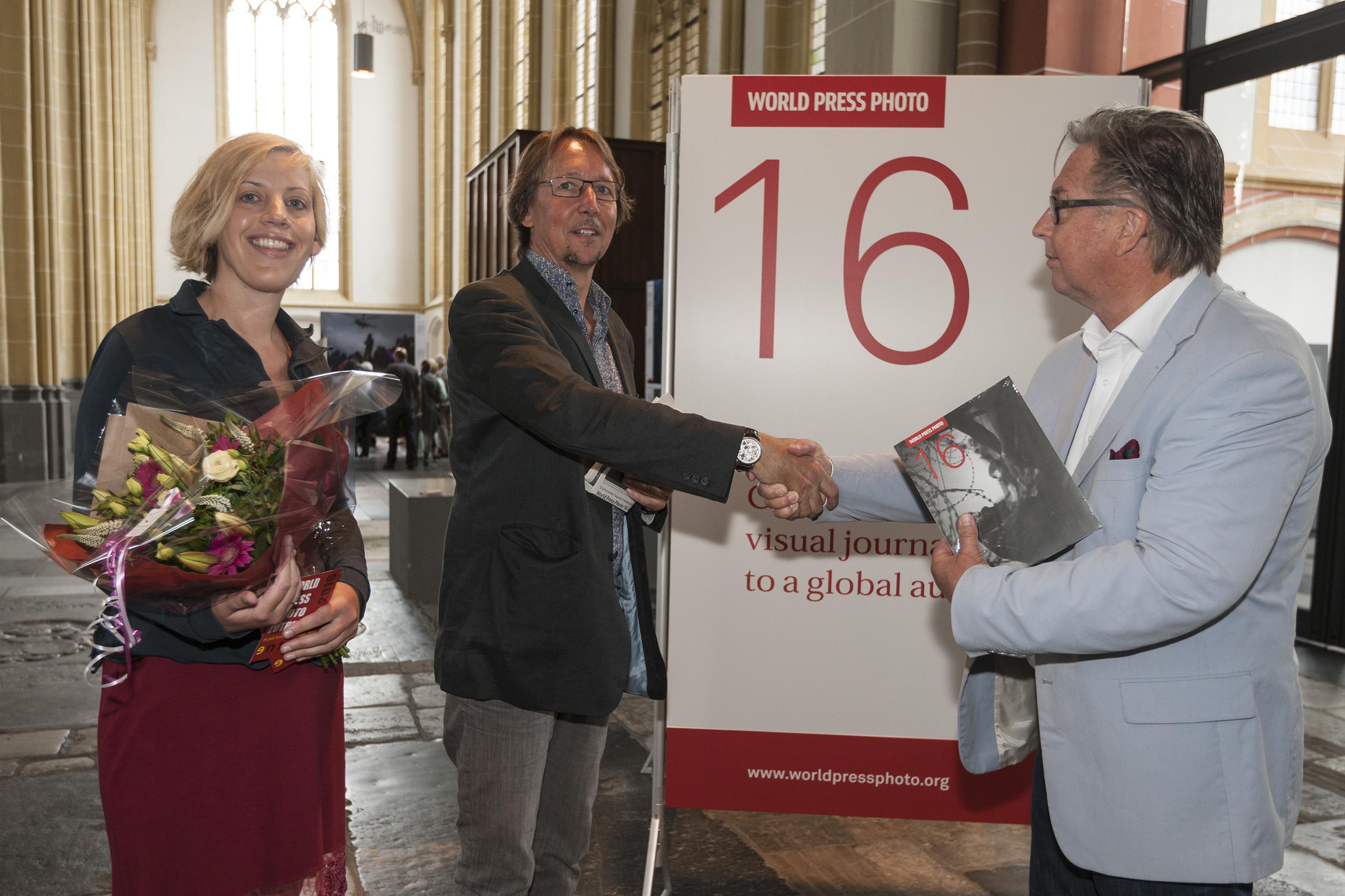 Voorzitter Peter Meulenbroek (rechts) overhandigt de 10.000ste bezoeker van de World Press Photo Zutphen bloemen en een fotoboek. (foto Patrick van Gemert/Zutphens Persbureau)