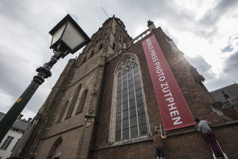 De World Press Photo tentoonstelling is vanaf 15 juli weer tezien in de Zutphense Walburgiskerk. Vandaag is de metershoge banier weer opgehangen aan de gevel van de tentoonstellingslocatie. (foto Patrick van Gemert/Zutphens Persbureau)